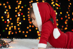 Baby crawl in christmas decoration, dressed as Santa, boke lights on dark background, winter holiday concept Stock Images