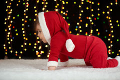 Baby crawl in christmas decoration, dressed as Santa, boke lights on dark background, winter holiday concept Royalty Free Stock Image
