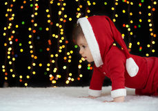 Baby crawl in christmas decoration, dressed as Santa, boke lights on dark background, winter holiday concept Royalty Free Stock Photo