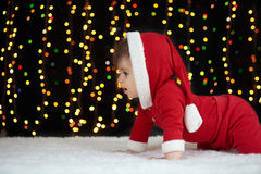 Baby crawl in christmas decoration, dressed as Santa, boke lights on dark background, winter holiday concept Stock Photo