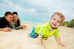 Baby crawling at the beach. Baby boy crawling in the beach, his parents look  at him happily Stock Photography