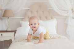 Baby crawling on the bed Stock Photo