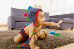Baby crawling on carpet and one hand up Royalty Free Stock Images