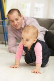 Baby crawling on floor Stock Photos