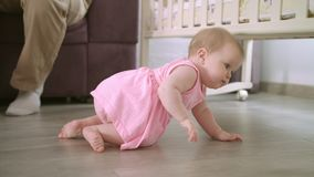Baby crawling on floor at home. Sweet childhood. Toddler walking in home