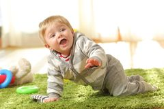 Baby crawling on a green carpet at home royalty free stock image
