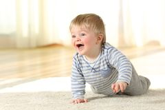 Baby crawling and laughing on the floor at home Stock Photos