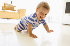 Baby crawling in living room. Smiling royalty free stock image