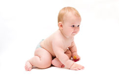 Baby crawling with a pacifier in his hands. Naked baby crawling on the floor intently with red pacifier in his hands royalty free stock photo