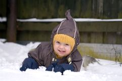Baby crawling in snow. (winter leisure Royalty Free Stock Images