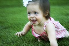 Baby crawling time. Slightly blurred action photo of a happy baby crawling on grass royalty free stock image