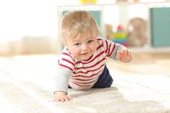 Baby crawling towards camera on the floor Stock Photo