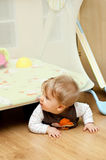 Baby crawling under playpen. Cute baby girl crawling under playpen in room Royalty Free Stock Images