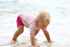 Baby crawling in water. Baby girl crawling on her hands in water royalty free stock photos