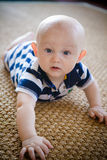 Baby Crawling on Woven Rug Stock Image