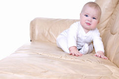 Baby  crawls on a leather sofa. Royalty Free Stock Images