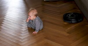 Child actively crawling near robot vacuum cleaner. Baby crawls on wooden floor. Robot vacuum cleaner does cleaning stock video