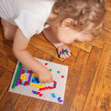 Baby creating a house of mosaics Royalty Free Stock Photography