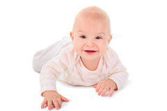 Baby is creeping on all fours, looking and smiling Royalty Free Stock Photography