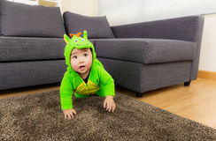 Baby creeping with dinosaur dressing Royalty Free Stock Photo