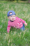 Baby creeps on grass in summer Stock Image