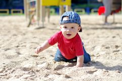 Baby creeps on playground. In summer Royalty Free Stock Photography