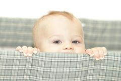 Baby in Crib. Baby peeking from above the crib railing, looking Stock Photography