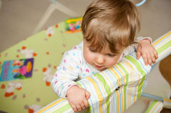 Baby in crib. Baby holding on to edge of crib Royalty Free Stock Images