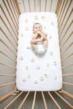 Baby in Crib. Baby sucking on feet in crib with flowered daisy sheets, caucasian/white Royalty Free Stock Image