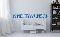 Baby crib and german Kinderwunsch on wall Stock Photos