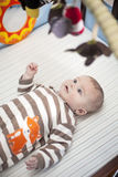 Baby in crib looking at toys Stock Images