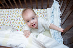 The baby is in the crib and looking up stock image