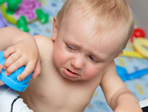 Baby cries holding a toy Royalty Free Stock Images