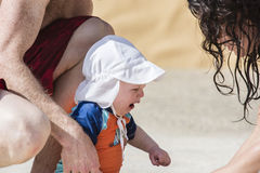 Baby Cries and Mother and Father Offer Comfort. A baby cries while on the beach in Mexico. Mom and dad offer comfort and love Stock Photo