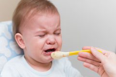 Baby cries and refuses to eat vegetable puree. The naughty kid is fussy and refuses to eat royalty free stock photography