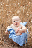 Baby crossing feet in basket. Happy talking baby in basket on a blue blanket with feet crossed Stock Images
