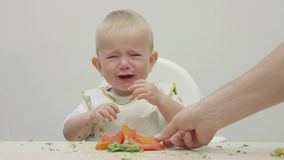 Baby cry in baby chair, mother hand offer food, difficult food diversification. 4K stock video