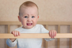 Baby cry in cot. Crying baby boy is standing in cot bed Stock Photography