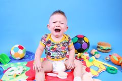Baby crying. The baby is crying on a blue background Royalty Free Stock Photo