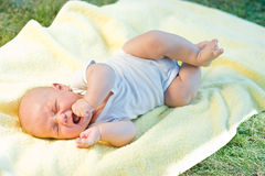 Baby crying. In a yellow towel in grass Stock Photo