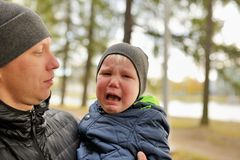 Baby crying in arms of his father in park.  stock images