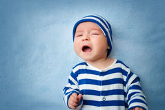 Baby crying in bed Stock Photos