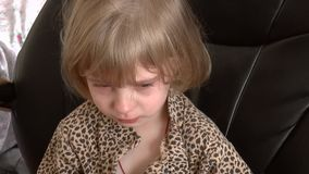 Baby crying on a black chair stock footage