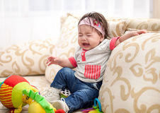 Baby is crying. A baby crying on the couch at home stock photos