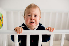 Baby crying in the crib Royalty Free Stock Images