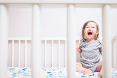 Baby Crying in Crib. Baby crying and screaming as seen through the bars of her crib Stock Photography
