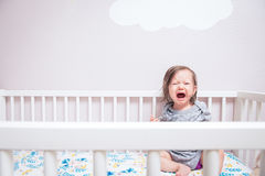 Baby Crying in Crib. A baby wakes up in her crib crying and screaming under a cloud on the wall Royalty Free Stock Photography