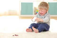 Baby crying in danger after eating some pills. Sad baby crying in danger after eating some pills from a bottle on the floor at home Royalty Free Stock Images