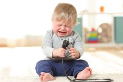 Baby crying holding an an electric plug. Front view portrait of a baby aby in danger crying holding an an electric plug sitting on the floor at home royalty free stock photos