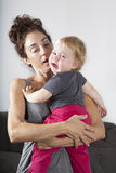 Baby crying in mom arms Stock Photo
